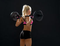 Sporty woman exercising with barbell from back Stock Photo