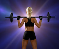Sporty woman exercising with barbell from back Stock Photos
