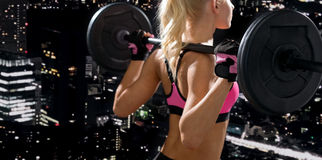 Sporty woman exercising with barbell from back Stock Images
