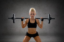 Sporty woman exercising with barbell Stock Photo