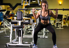 Sporty woman exercising with barbell in gym. Stock Photography