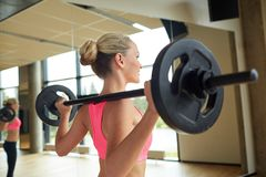 Sporty woman exercising with barbell in gym Royalty Free Stock Image