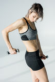 Sporty woman exercising with dumbbells and looking at muscles on grey Royalty Free Stock Image