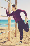 Sporty woman exercising at sea beach Stock Images