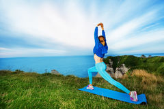 Sporty woman exercising on the top of cliffs Royalty Free Stock Image