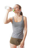 Sporty woman in fitness dress is drinking water from a water bottle. Isolated on white Royalty Free Stock Images