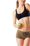 Sporty woman in fitness dress holding green apple. Isolated on white Stock Images