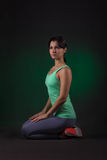 Sporty woman, fitness woman sitting on a dark background with green backlight Royalty Free Stock Image