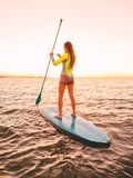 Slim woman floating at stand up paddle board in sea with warm sunset colors. Sporty woman floating at stand up paddle board with colorful sunset stock images