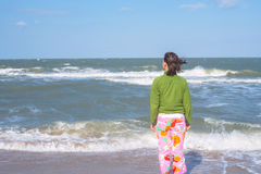 Sporty woman with flying hair is standing in the surf Stock Images