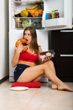 Sporty woman by the fridge. Woman standing by the fridge and choosing products royalty free stock images