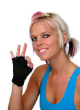 Sporty woman gesturing okay. Portrait of sporty young woman with blond hair in training top and fingerless gloves gesturing okay; isolated on white background Stock Photo