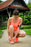 Sporty woman getting ready for running at city park Stock Image