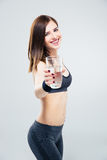 Sporty woman giving glass of water on camera Royalty Free Stock Image