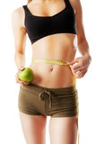 Sporty woman with green apple in hand measuring her waist Stock Photos