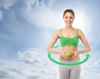 A sporty woman with a green apple on a sky bac Royalty Free Stock Photos