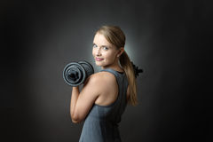 Sporty woman on grey background with dumbbells Royalty Free Stock Photos