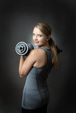 Sporty woman on grey background with dumbbells Royalty Free Stock Photography