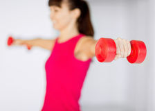 Sporty woman hands with light red dumbbells Stock Image