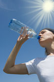 Sporty woman have water from bottle. Over blue sky Royalty Free Stock Images
