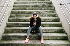 Sporty woman with headhphones texting on smartphone Stock Photos