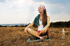 Sporty woman with headphones meditates Royalty Free Stock Image