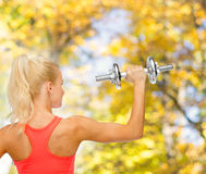 Sporty woman with heavy steel dumbbell from back Stock Photography