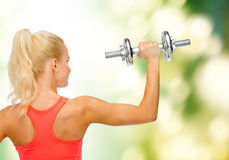 Sporty woman with heavy steel dumbbell from back Royalty Free Stock Photos