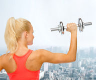 Sporty woman with heavy steel dumbbell from back Royalty Free Stock Images