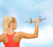 Sporty woman with heavy steel dumbbell from back Stock Image