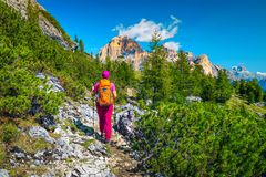 Sporty woman hiker with backpack, walking in mountains, Dolomites, Italy stock photos