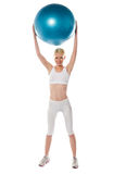 Sporty woman holding ball over her head Stock Photography