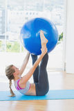 Sporty woman holding exercise ball between ankles in fitness studio Royalty Free Stock Image