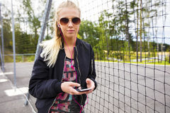 Sporty Woman Holding Mobile Phone While Listening Music By Fence Stock Images