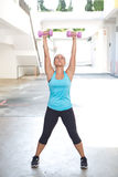 sporty woman holding pink barbell with both arms stretched out for shoulder strengthening, outdoors. Royalty Free Stock Photo
