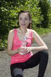 Sporty woman holding a water bottle during a break Royalty Free Stock Photography