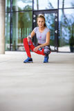 Sporty Woman Holding Water Bottle While Crouching On Footpath Stock Photography