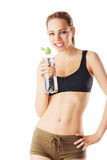 Sporty woman holding water bottle and smiling straight into the camera Royalty Free Stock Images