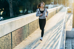 Sporty woman jogging in city Stock Images