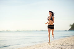 Sporty woman jogging on seaside Stock Images