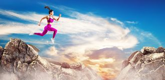 Sporty woman jump through the gap between hills over sky background. stock photo