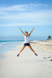 Sporty woman jumping at beach Royalty Free Stock Photos