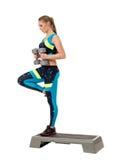 Sporty woman keeps balance standing on one leg Stock Photo
