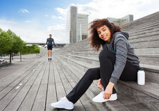 Sporty woman lacing her shoes sitting on staircase Stock Photos