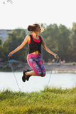 Sporty woman on the lakes coast makes exercise using a jump rope on the sunset Stock Photography