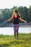 Sporty woman on the lakes coast makes exercise using a jump rope on the sunset Stock Photo