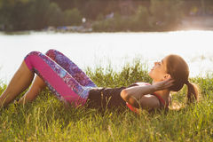 Sporty woman on the lakes coast makes sport exercises on the sunset Royalty Free Stock Images