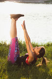 Sporty woman on the lakes coast makes sport exercises on the sunset Royalty Free Stock Photography