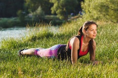 Sporty woman on the lakes coast makes sport exercises on the sunset Stock Photography