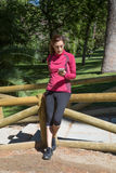 Sporty woman leaning in wooden railing using mobile Royalty Free Stock Photos